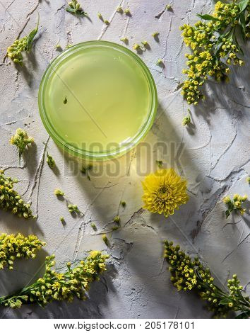 Green moisturizing cosmetic mask on the painted wooden background with yellow flowers around