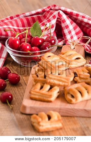 Cherry pastry pies with jam on cuttingboard.