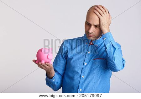 Worried Businessman Looking At Piggy Bank