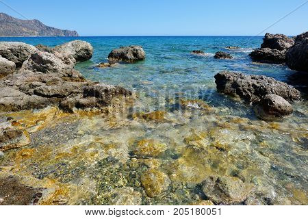 Still sea shore with blue water and stones