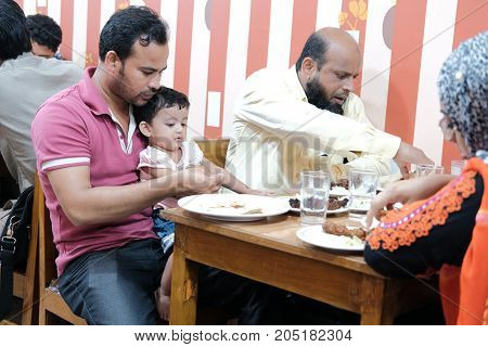 Dhaka, bangladesh september 17- muslim family eating dinner together at local resturent located at motikhil area in dhaka in bangladesh taken on 17th september 2017