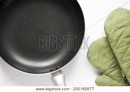 Top View a pan and green glove on white background
