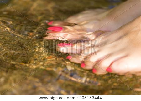 pedicure on foot in the water on the rocks .