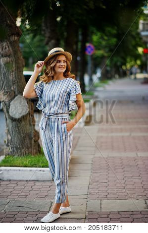 Portrait Of A Very Attractive Young Woman In Striped Overall Posing With Her Hat On A Pavement In A