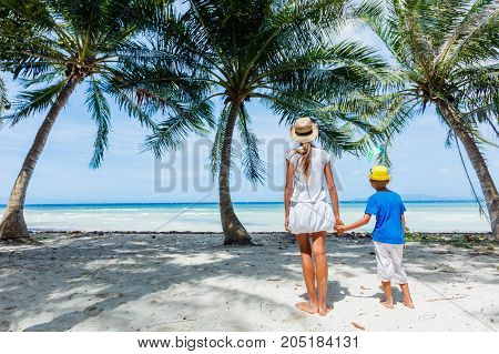 Cute sister and brother having fun on a white sand tropical beach with palms tree