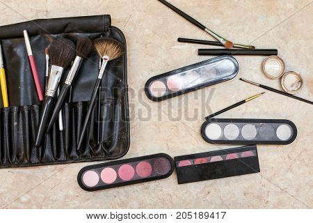 Set of professional colorful cosmetics and makeup brushes for visage