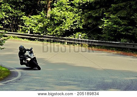 picture of biker on motorcycle riding through curve