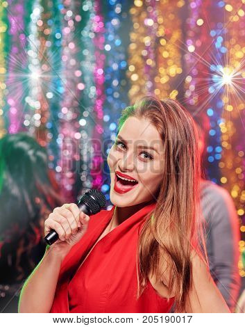 Portrait of beautiful stylish girl singing karaoke with friends at the club