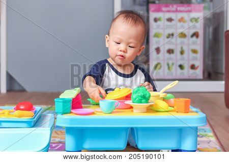 Portrait of Cute little Asian 18 months / 1 year old toddler baby boy child having fun playing alone with cooking toys in living room at home Educational toys for young kids concept