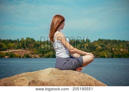 Beautiful young smiling woman with long red hair, wearing striped skirt and white top, sitting on a stone cliff, enjoying river view