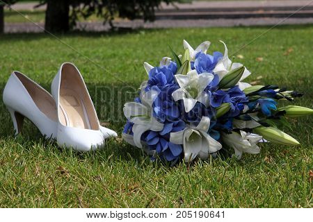 Wedding shoes and bouquet on green grass on a sunny day