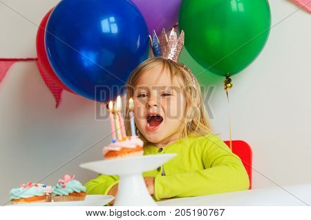 happy cute little girl make wish blow candles at birthday party