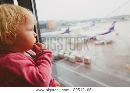 where to go next, travel concept- baby thinking looking at planes in airport