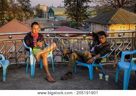 Young Men Relaxing At Coffee Shop In Sunset