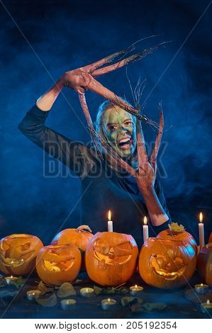 Halloween costume woman, tree girl, female with hands branches with burning pumpkins in front of her grinning making scary face on smoky background