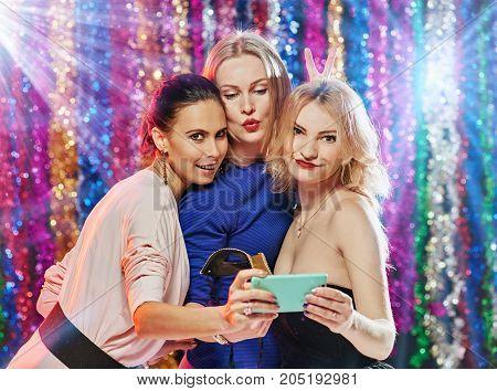 Group of happy beautiful girlfriends making selfie in night club