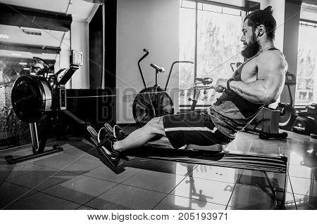 Bearded Muscular Fit Man Ssing Rowing Machine at Functional Training Gym