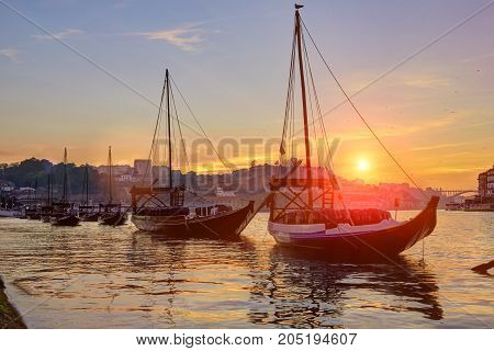 Porto old town skyline on the Douro River with rabelo boats at sunset, Portugal
