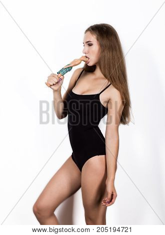Sensual young woman in a swimsuit holding a doll and bite off her head.
