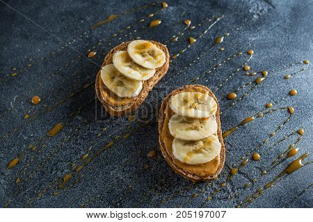 Sandwich with peanut butter, banana and caramel. Vegetarian natural breakfast. Flat lay, top view