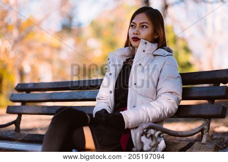 Portrait of young beautiful woman sitting on the bench in stylish warm outfit in sunny autumn day in park. Casual lifestyle in the city