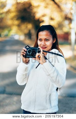 Beautiful girl in white woolen coat photographing outside on the street during autumn afternoon