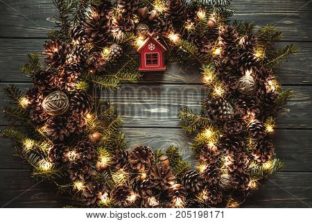 Christmas wreath with lights garland . Homemade creative handmade decor for home. Holiday tradition.Dark toned photo. Xmas evening dinner.