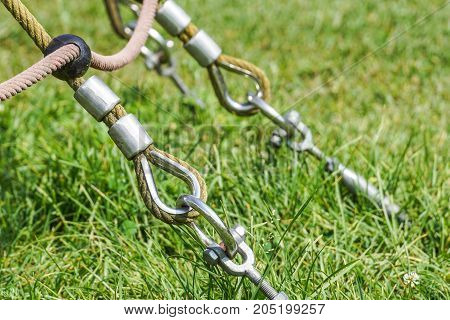 End of swinging rope hang on metal construction in a park. Rough rope end in metal circles and safety snap hook .