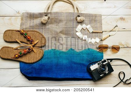Flat lay of summer fashion with camera slippers sunglasses and other girl accessories on top of the bag on white wooden background