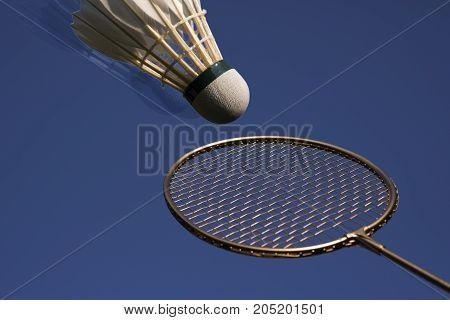 Badminton racket and shuttlecock high up and sky blue.