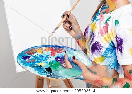 hand of the female artist holding a palette with paints for drawing in front of the easel