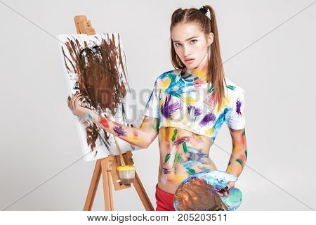 portrait of beautiful young woman artist soiled in colorful paint draws on canvas.
