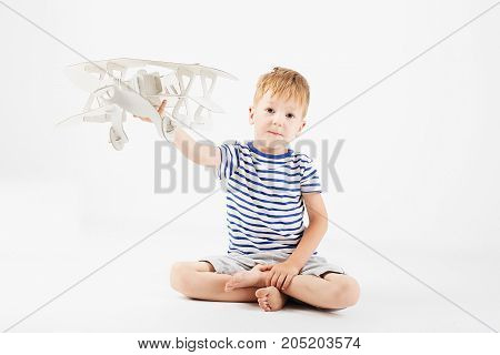 Child Boy Playing With Paper Toy Airplane Sitting On The Floor Against A White Background. Kid Dream