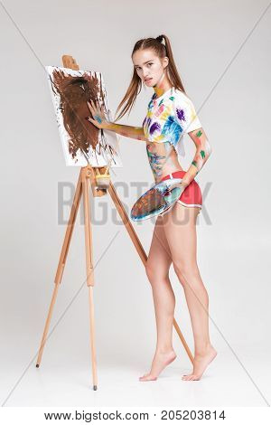 beautiful young woman artist soiled in colorful paint draws on canvas.