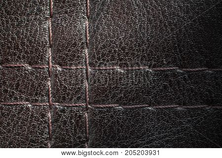 Leather with thread macro texture. Dark surface of leather furniture