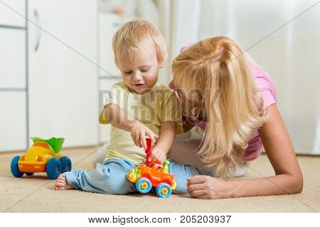 Cute child boy and mother repairing toy car at home