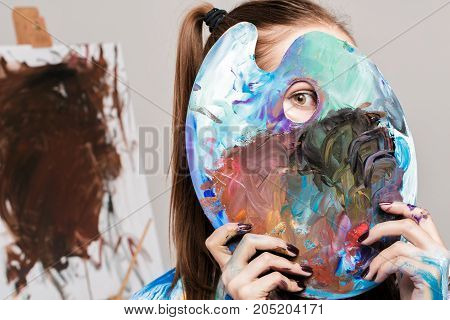 beautiful woman artist soiled in multicolored paint holds a palette with paints in front of her face
