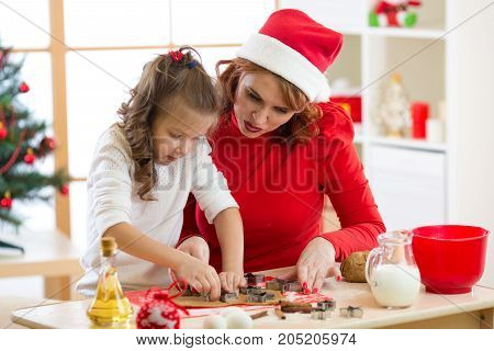 Happy woman and child girl cutting christmas cookies out of dough together