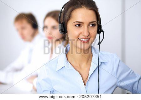 Call center. Focus on beautiful woman in headset.