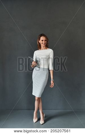 Young and smart. Full length of confident young woman in smart casual wear holding digital tablet and smiling while standing against grey background