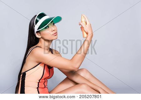Woman In Swimsuit And Visor With Sunscreen Bottle