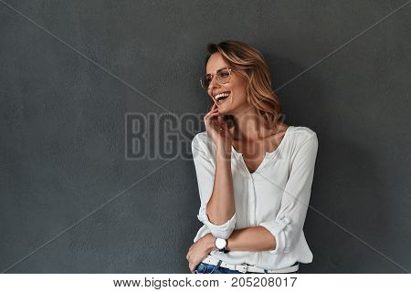 Feeling free and happy. Attractive young woman in casual wear looking away and smiling while standing against grey background