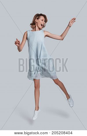 Beauty in motion. Full length of playful young woman gesturing and keeping mouth open while jumping against grey background