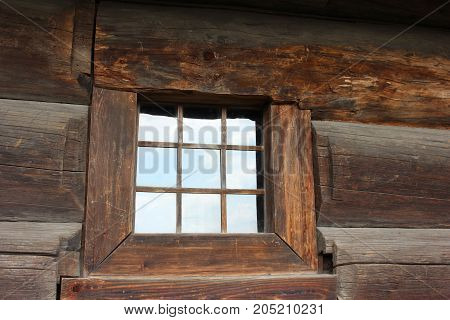 Partitioned window of old traditional house. Mountain traditional house detail. Solid wooden wall with window.