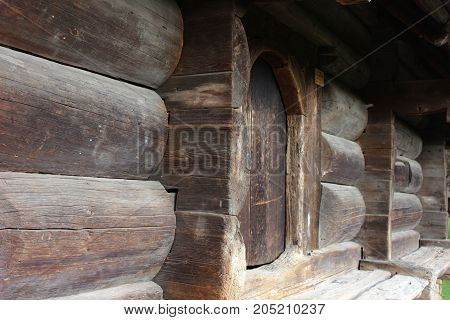 Old entrance door of traditional wooden house. Solid ancient traditional house walls and door.