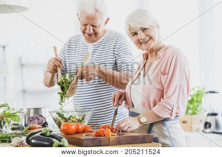 Grandma Cuts Pepper And Grandpa Mixes Salad
