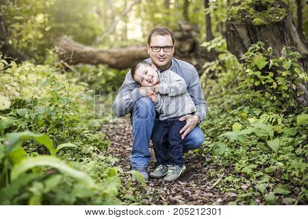 A Little boy and his father on grass in autumn forest