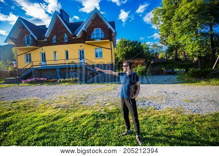 Happy young businessman in sunglasses bought a big home. Man standing with laptop near his new home and point on something
