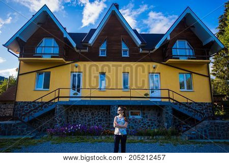 Happy young businesswoman in sunglasses bought a big home. Woman standing near her new home