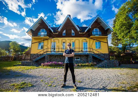 Happy young businessman in sunglasses bought a big home. Man standing with thumbs up near his new home